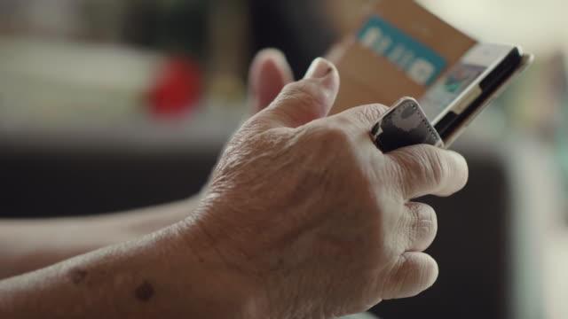 großmutter verwendung smartphone zu hause. - großmutter stock-videos und b-roll-filmmaterial