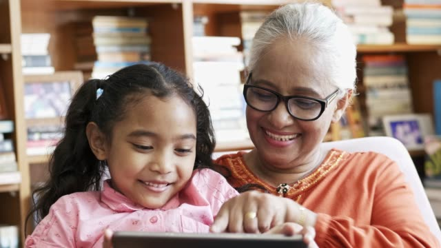 grandmother using digital tablet with girl - multi generation family stock videos & royalty-free footage