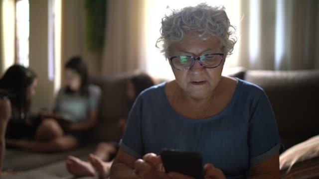 vídeos de stock, filmes e b-roll de avó usando celular em casa - aconchegante