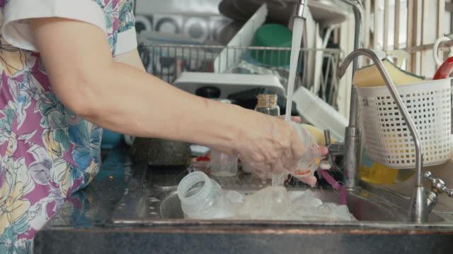 vídeos y material grabado en eventos de stock de abuela usando spume limpiar una botella de leche para su hija abuela - sencillez