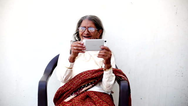 grandmother video calling on smartphone - indian subcontinent ethnicity stock videos & royalty-free footage