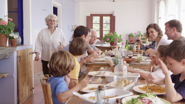 grandmother walking towards grandsons at table - tipo di cibo video stock e b–roll