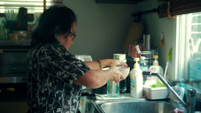 grandmother washing the dishes in the kitchen sink at home - washing up stock videos and b-roll footage