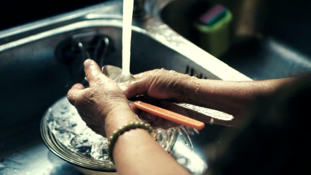 grandmother washing the dishes in the kitchen sink at home - lavori di casa video stock e b–roll