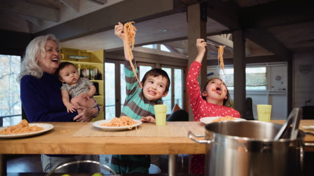 Grandmother watching messy grandchildren eating spaghetti