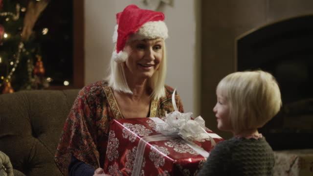 ms grandmother wearing santa hat giving present to girl (2-3) in living room / cedar hills,utah,usa - santa hat stock videos and b-roll footage