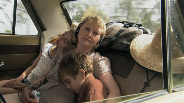 vídeos y material grabado en eventos de stock de ms, grandmother with boy (6-7) and girl (10-11) sleeping on car back seat, tamborine mountain, brisbane, queensland, australia - auriculares equipo de música