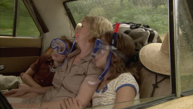 ms, grandmother with boy (6-7) and girl (10-11) wearing snorkeling gear sleeping on car back seat, tamborine mountain, brisbane, queensland, australia - napping stock-videos und b-roll-filmmaterial