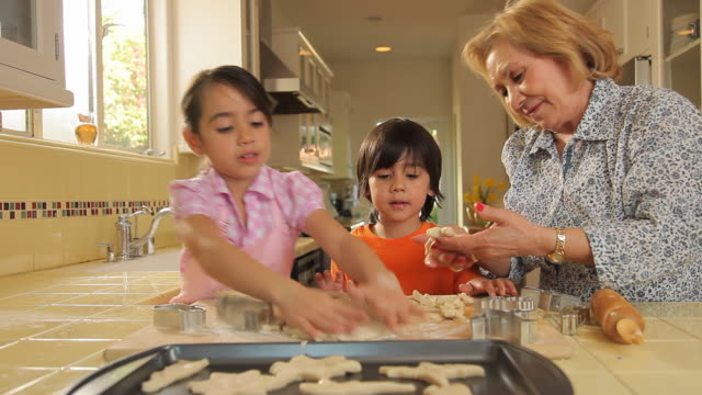MS Grandmother with children making cookies stamping out shapes / Los Angeles, California, USA