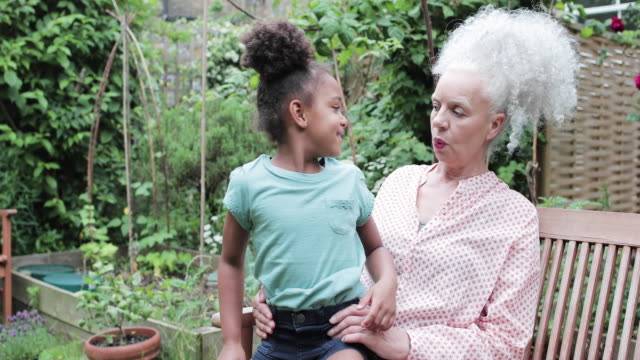 grandmother with grandchild in garden - bench stock videos & royalty-free footage