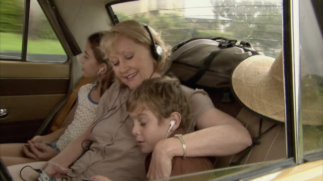 ms, grandmother with granddaughter (10-11) and grandson (6-7) listening to music on car back seat, tamborine mountain, brisbane, queensland, australia - ascoltare video stock e b–roll