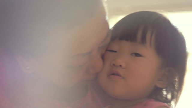 grandmother with granddaughter kissing cheek - grandchild stock videos & royalty-free footage