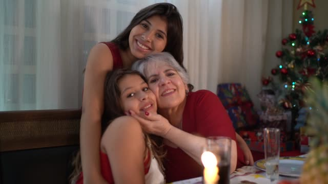 grandmother with granddaughters portrait at christmas dinner - three people stock videos & royalty-free footage