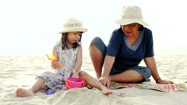 Grandmother with granddoughter playing with sand on the beach