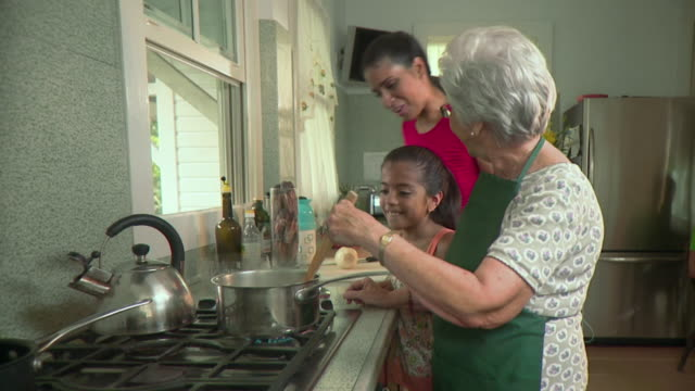 ms grandmother with mother and daughter (6-7) cooking in kitchen, panama city, panama  - cucina domestica video stock e b–roll