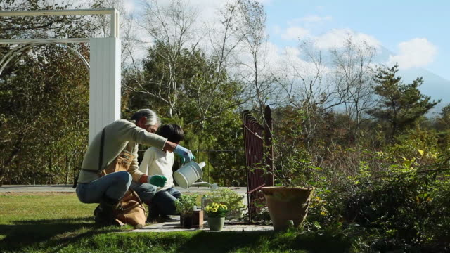 vídeos de stock e filmes b-roll de ms grandpa and grandchild are doing gardening in garden / fujikawaguchiko, yamanashi, japan - vida simples