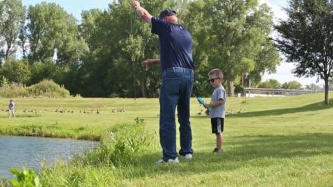 vidéos et rushes de grandpa and grandson fish - étang