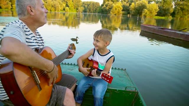 opa und enkel spielen gitarre - gitarre stock-videos und b-roll-filmmaterial