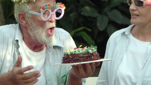 おじいちゃんは彼の誕生日ケーキにろうそくを吹き消す - コメディアン点の映像素材/bロール