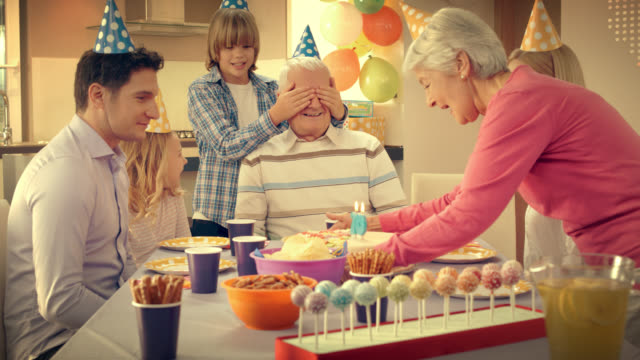 vídeos de stock e filmes b-roll de ao avô como surpresa bolo de aniversário com a família - jovem de espírito