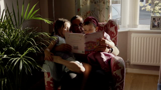 stockvideo's en b-roll-footage met grandpa reading a story to his grandchildren - panty