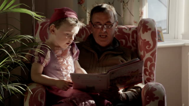 grandpa reading a story to his grandchildren - storytelling stock videos and b-roll footage