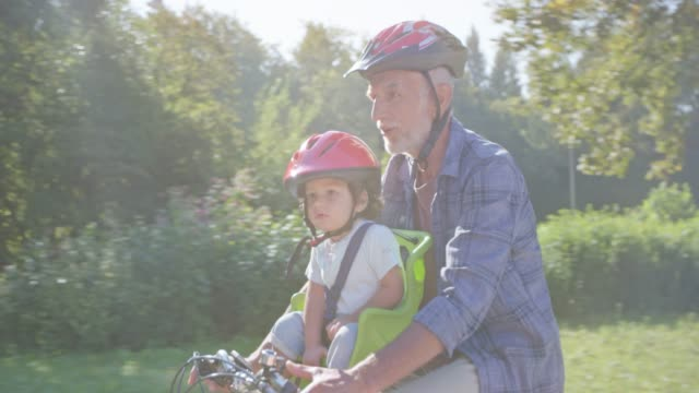 ts grandpa riding his bike in the sunny park with his toddler grandson ringing the bell while sitting in the front seat - grandfather stock videos & royalty-free footage