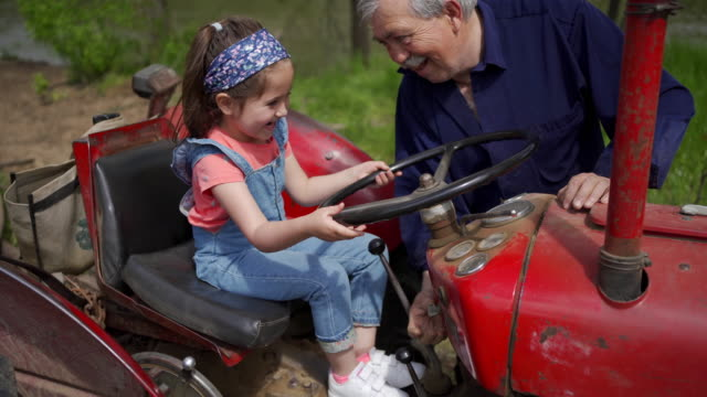 grandpa showing to his curious granddaughter how to start an engine at tractor vehicle - candid stock videos & royalty-free footage