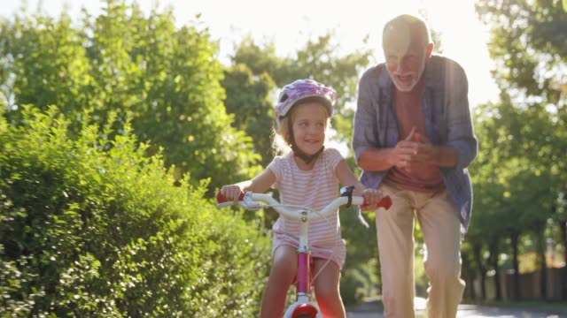 slo mo ds grandpa teaching young granddaughter how to ride a bike and clapping his hands with joy - grandfather stock videos & royalty-free footage
