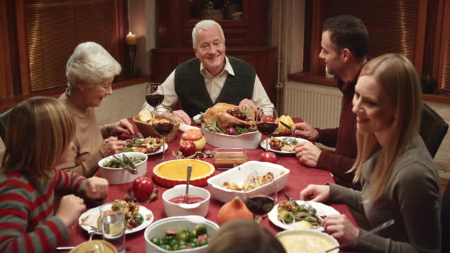 Grandpa telling a story at Thanksgiving dinner