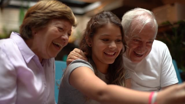 grandparent and granddaughter taking a selfie at home - granddaughter stock videos & royalty-free footage