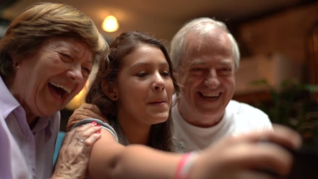 grandparent and granddaughter taking a selfie at home - ridere video stock e b–roll