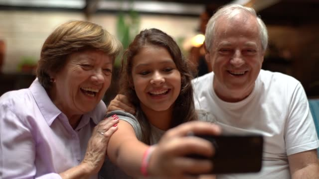 grandparent and granddaughter taking a selfie at home - latin american culture stock videos & royalty-free footage