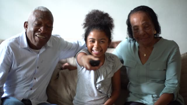 grandparent and granddaughter watching tv on sofa at home - three people stock videos & royalty-free footage
