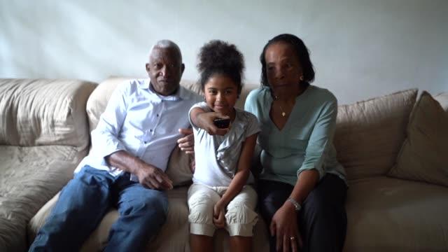 vídeos de stock, filmes e b-roll de avô e neta assistindo tv no sofá em casa - assistir tv