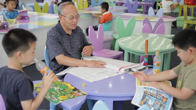 A grandparent discusses geography as they sit at a table in the Tianjin Library.