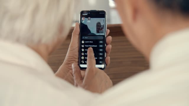 grandparent talks to grandchild on smart phone at home - grandson stock videos & royalty-free footage