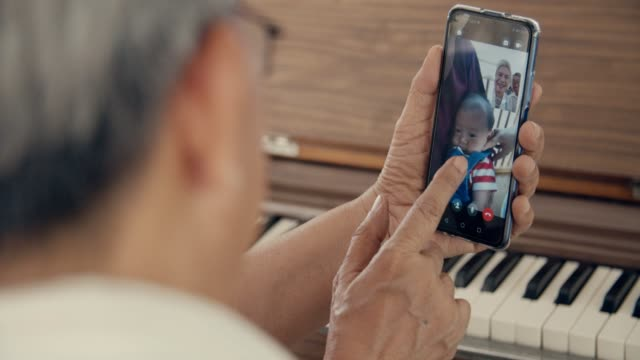 grandparent talks to grandchild on smart phone at home - usare il telefono video stock e b–roll
