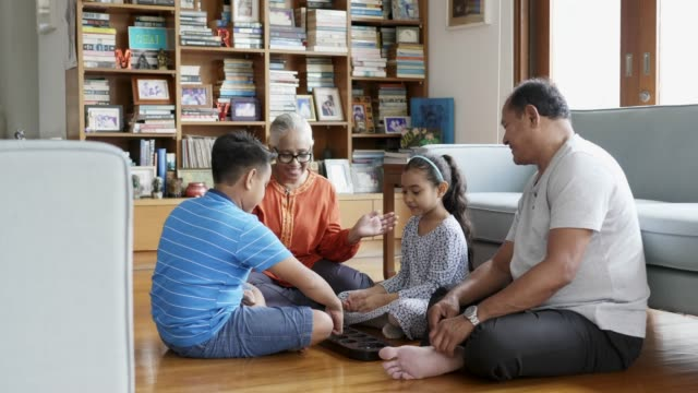 grandparents and children having fun in mancala - malay family stock videos and b-roll footage
