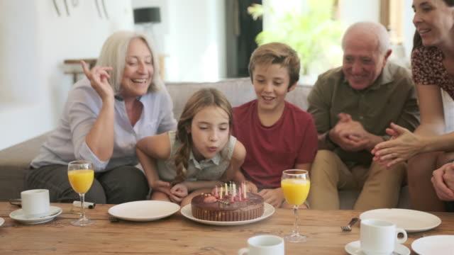 vidéos et rushes de grands-parents et père observant comme fille souffle dehors des bougies - famille multi générations