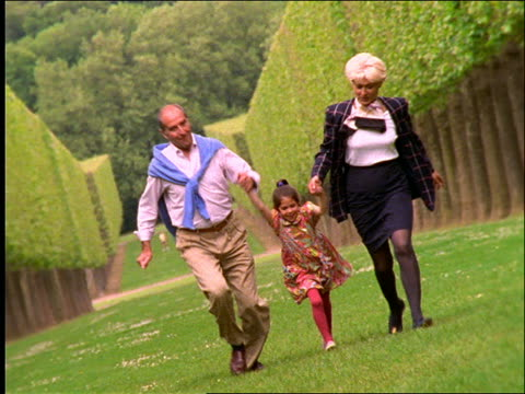 vídeos de stock e filmes b-roll de grandparents and girl holding hands and running in grass / paris - 1990