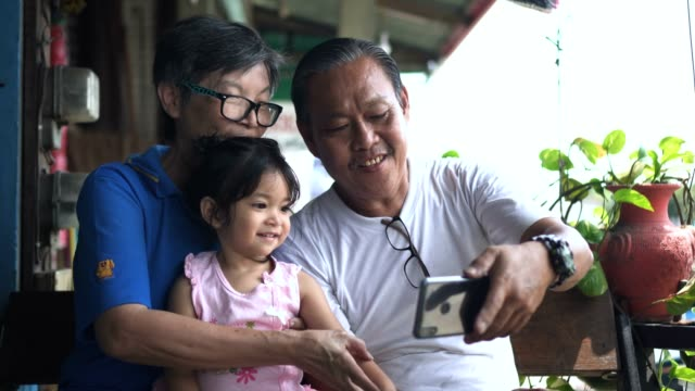grandparents and grandchild making a selfie with smartphone - senior couple stock videos & royalty-free footage