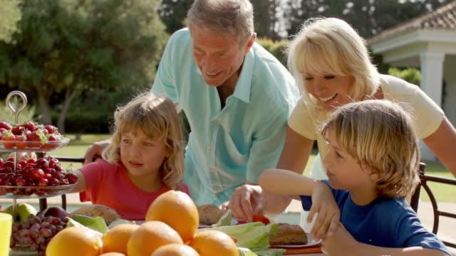 vidéos et rushes de grandparents and grandchildren walking to table of food in garden. - déjeuner