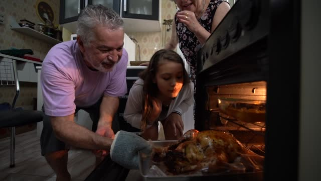 vídeos de stock e filmes b-roll de grandparents and granddaughter checking the traditional turkey for christmas dinner - jantar comida e bebida