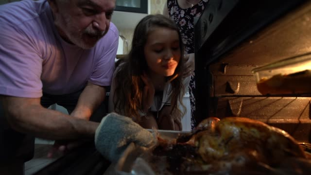 grandparents and granddaughter checking the traditional turkey for christmas dinner - latin american culture stock videos & royalty-free footage