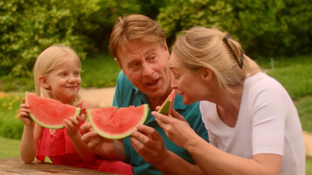 Grandparents and granddaughter eating watermelon in park
