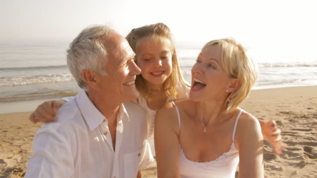 grandparents and granddaughter on beach