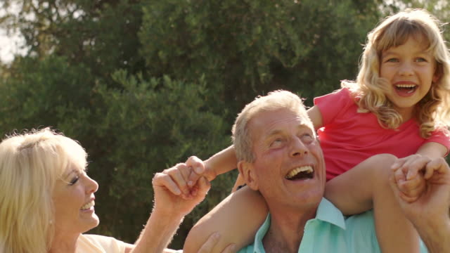 grandparents and granddaughter playing on grandfathers shoulders in garden. - 肩車点の映像素材/bロール