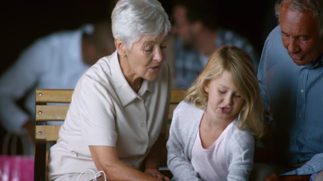 SLO MO von Großeltern mit Enkelin, auf einer Bank sitzend Lachen