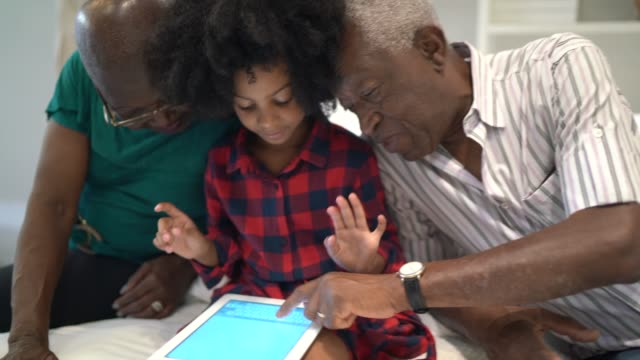 grandparents and granddaughter using digital tablet at bed - hanging mobile stock videos & royalty-free footage
